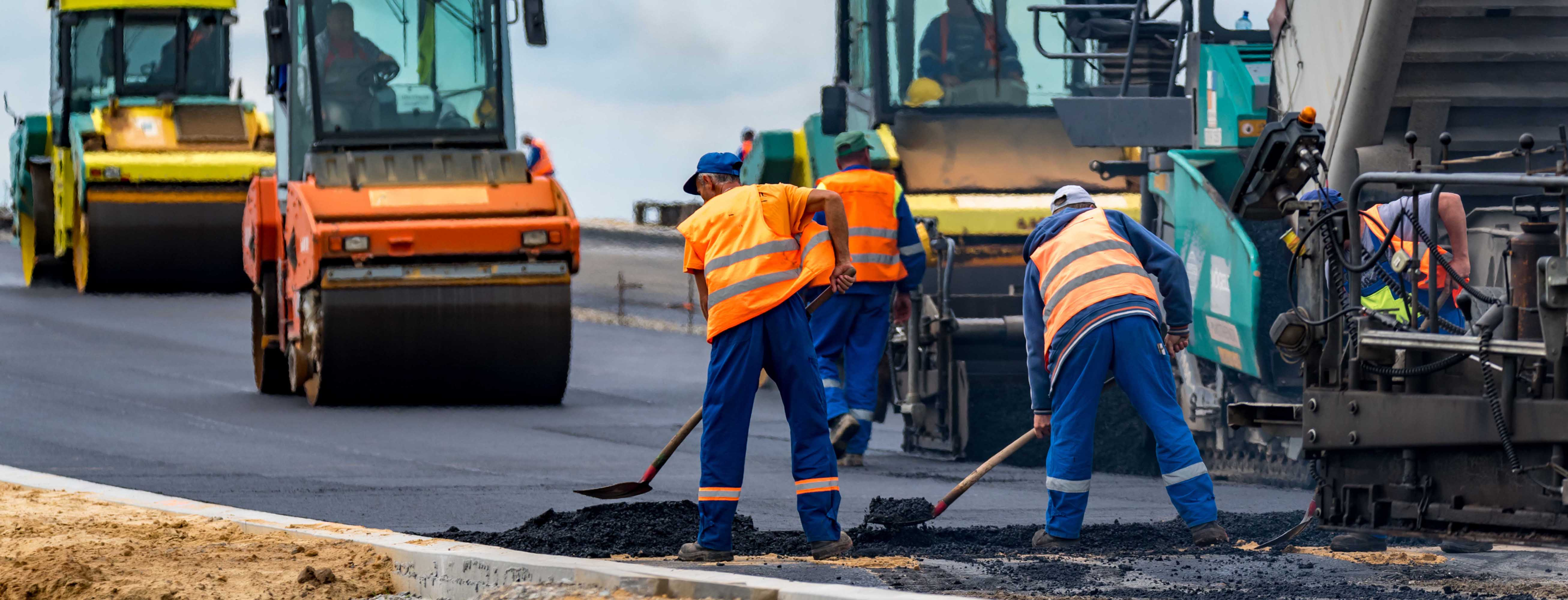 Several road workers in action. Shovelling tarmac.